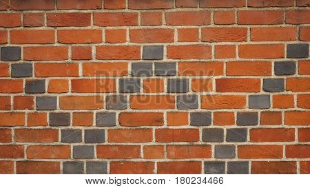 Letter W formed by pattern of black bricks in red brick wall