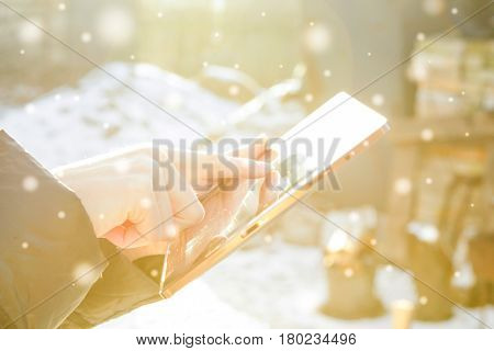 man flips through photos on a tablet On a winter sunny day. With snow