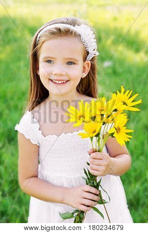 Adorable little girl on the meadow with flower in summer day