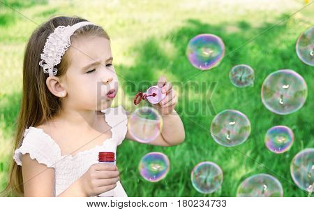 Adorable little girl is blowing a soap bubbles in summer day