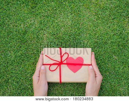 Hands holding beautiful gift box female giving gift Christmas holidays and greeting season concept shallow dof