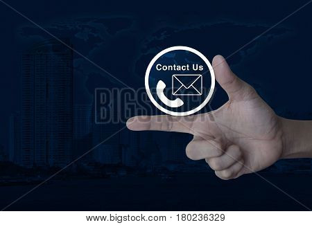 Telephone and mail icon button on finger over world map and modern city tower Contact us concept Elements of this image furnished by NASA
