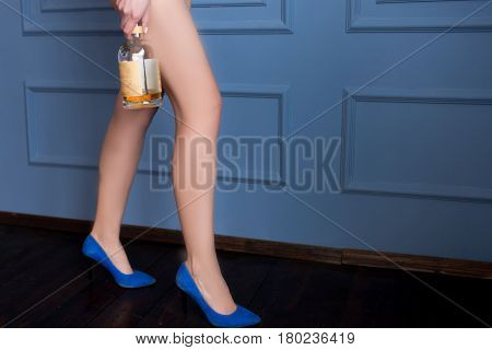 Long legged woman in blue shoes holds a nearly empty bottle of whiskey on a blue background