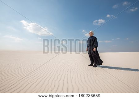 Man In Traditional Clothes Stands And Meditates In The Middle Of Desert
