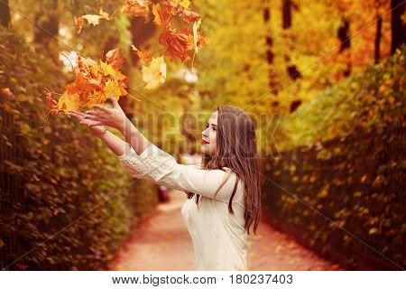 Autumn Pretty Woman Outdoors. Woman Fasion Model throwing Up Fall Leaves in the Park