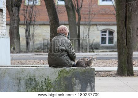 A woman and a young cat sit on a concrete foundation near the entrance in anticipation