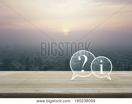 Question mark and information chat icon on wooden table over cityscape at sunset vintage style Customer support concept
