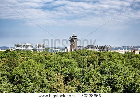 View on Olsany Jewish Cemetary covered by dense stand of trees and city architecture at the background Prague Czech Republic