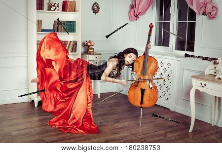 Beauty in mid-air. Full length studio shot of attractive young woman in orange dress hovering in air and playing the cello.