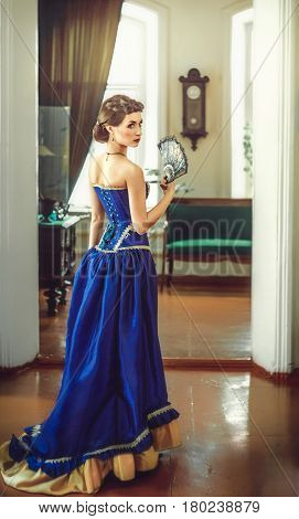 Young beautiful luxurious woman in long elegant dress .Beautiful young woman in a luxurious classic interior. Seductive brunette woman in luxury manor, vintage style