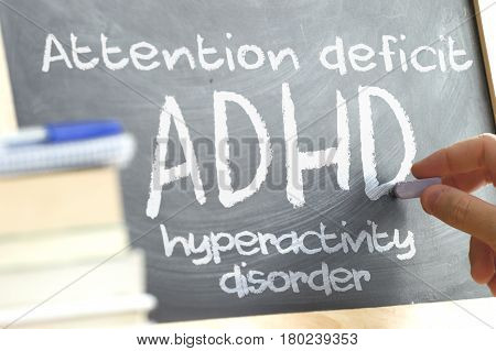 Hand writing on a blackboard in a class with the word ADHD written on. Some books and school materials.Attention Deficit Hyperactivity disorder concept.