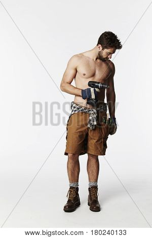 Construction worker shirtless with tools studio shot