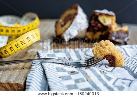 piece of cake impaled on a fork with a measuring tape on a side and broken half-eaten cake at the background