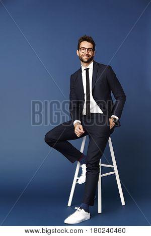Businessman on stool in studio portrait studio shot
