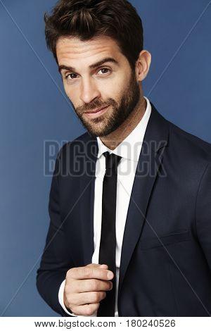 Portrait of businessman with stubble smiling studio shot