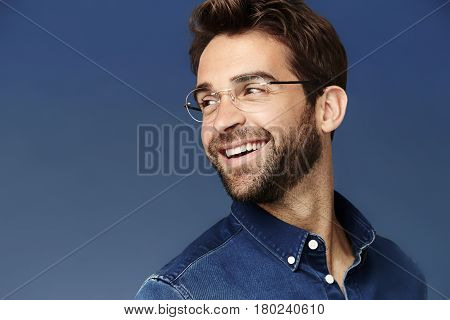 Dude in denim shirt and glasses looking away