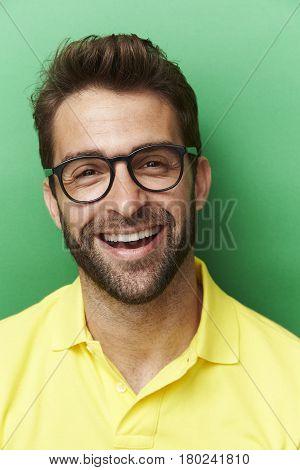 Happy chap in yellow top portrait studio shot