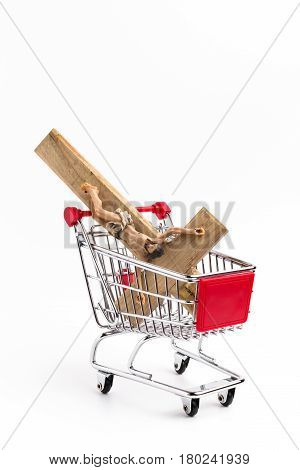 Crucifix in shopping cart. Conceptual representation of commodification of religion loss of faith blasphemy.