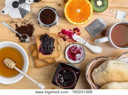 Breakfast table with mug of tea jam fresh fruits bread rusks and honey. Top view.