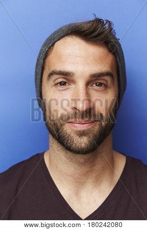Confident chap in hat portrait studio shot