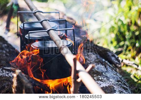 Cauldron boils on the fire camping in the forest. In marching a saucepan preparing food. Adventure tourismcooking on a fire. Survival in the forest. Travel concept.