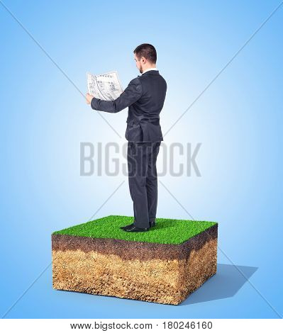 The concept of property. A man with drawing is standing on a piece of land. Concept of planning.