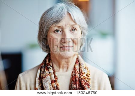 Head and shoulders portrait of pensive elderly woman in beige sweater and colorful kerchief on shoulders looking away while standing at window
