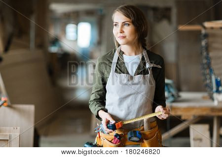 Portrait of thoughtful pretty carpenter with tool belt holding tape measure in hands and looking away in spacious workshop