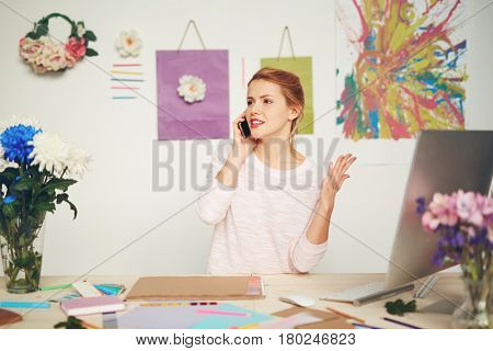 Serious graphic designer leading difficult telephone conversation with her client and gesticulating at the same time in colorful studio