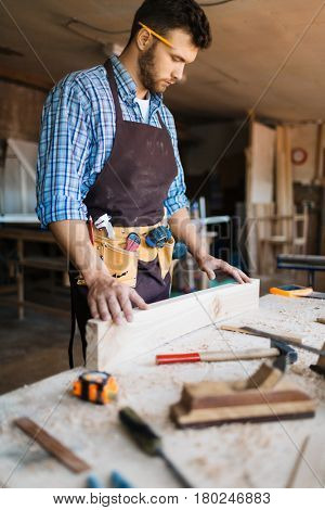 Bearded carpenter with pencil behind his ear checking surface of wooden board, table with shavings and hand tools on foreground
