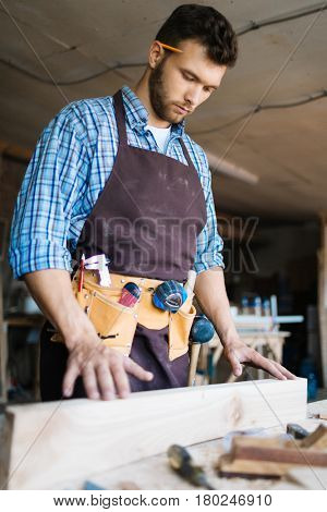 Concentrated young craftsman wearing tool belt and apron examining plank of wood while standing at workbench