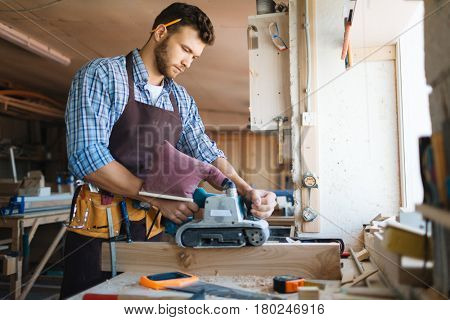 Waist-up portrait of young dark-haired craftsman wearing checked shirt working with belt sander in workshop, profile view