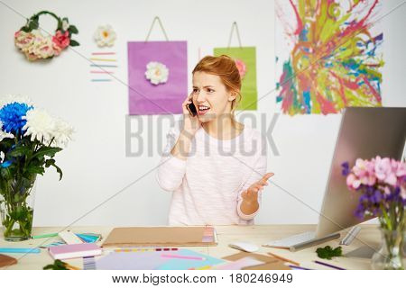 Annoyed female owner of design studio talking to her business partner on smartphone and gesticulating at the same time, abstract painting and flower decorations hanging on wall