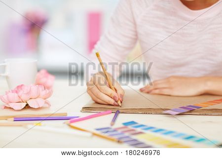 Close-up shot of female hands taking notes, color swatches, pencils and flowers lying on white desk