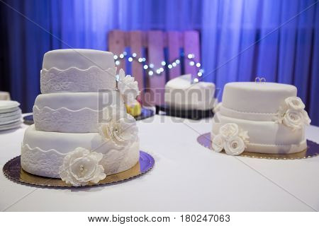 two white marzipan wedding cakes on a table