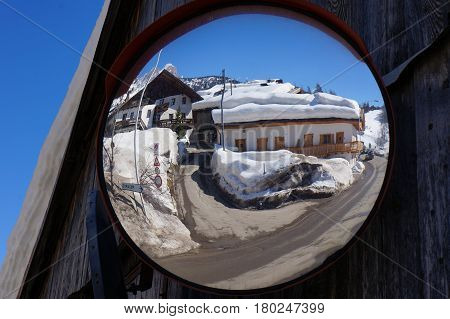 Reflection of houses near snow mountain slope on mirror. Cortina de Ampezzo. Italy