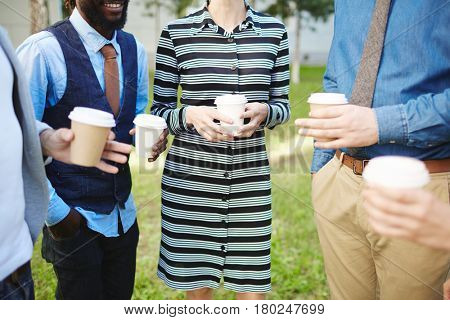 Cheerful colleagues spending short break outdoors: they drinking coffee from paper cups and chatting animatedly, close-up shot