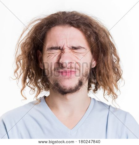 Basic emotions. Man expressing disgust on face, grimacing while standing against white studio background, cutout