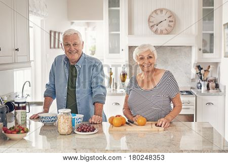 Portrait of a smiling senior couple preparing a healthy breakfast of fruit together while standing at their kitchen counter