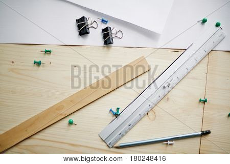 Above view of measuring supplies on table: rulers, pencil and paper laid out on engineering desk