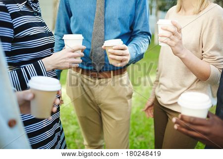 Multiethnic group of businesspeople gathered together in spring park with paper cups of coffee and having small talk, close-up shot