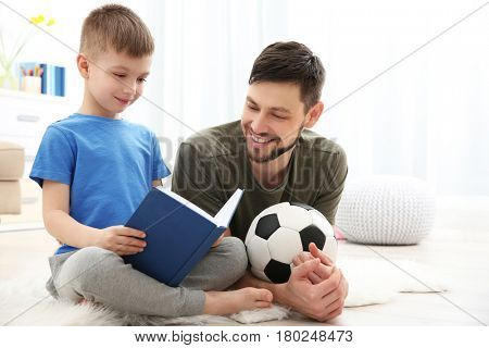 Father and son reading book at home