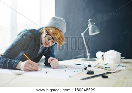 Portrait of young red haired designer wearing glasses and beanie hat working in office: leaning on desk with lamp and house model, drawing floor plan