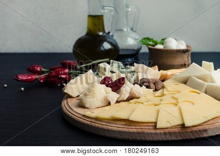 Cheese plate: Parmesan cheddar gouda mozzarella and other with chili pepper and almonds on wooden board with olive oil on the table. Tasty appetizers. Selective focus.