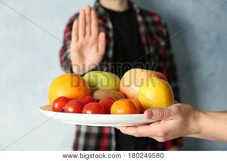 Allergy concept. Young man refusing to eat fruits and vegetable