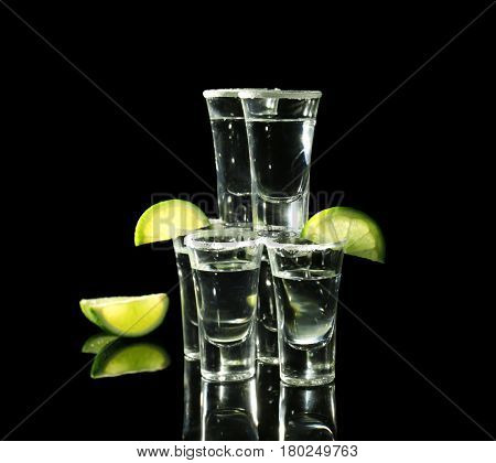 Tower of tequila shots with juicy lime slices and salt on black background