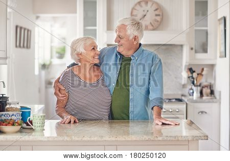 Affectionate senior couple looking at each other and smiling while standing happily together in their kitchen at home