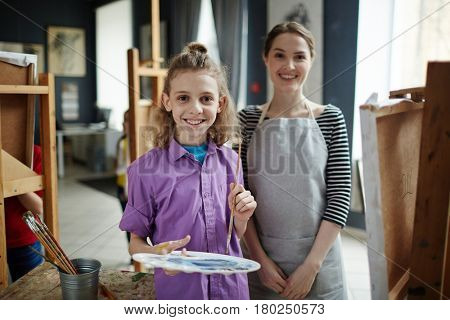 Happy schoolboy and his teacher of arts looking at camera in art class