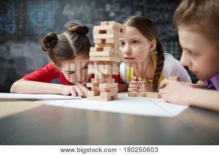 Curious girl looking at wooden brick tower being built by her school friends