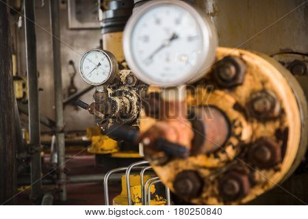 Selective focus of pressure gauge pressure gauge measuring gas pressure. Pipes and valves at oil and gas industrial plant.